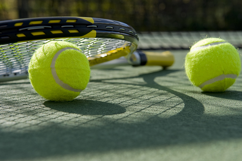 A group of tennis balls and a tennis racket on a freshly painted cement tennis court